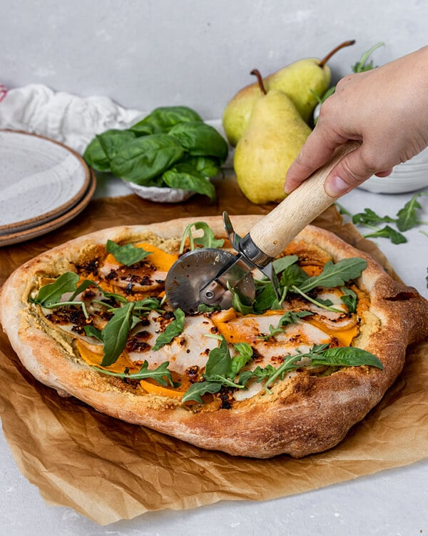 A Vegan pizza being sliced that is topped with vegan garlic cashew sauce, pear, butternut squash, chili oil, arugula, and basil