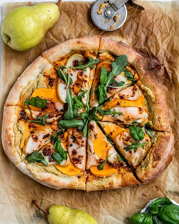 Slices of pizza topped with vegan garlic sauce, butternut squash slices, pear slices, chili oil, arugula, and basil