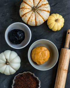 Bowls of charcoal and pumpkin cookie dough to make pinwheel cookies with a rolling pin, sprinkles, and pumpkins