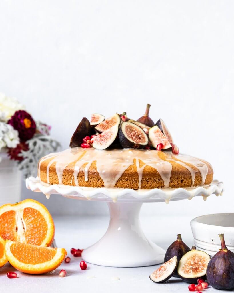 A One-Layer Vegan Orange Blossom Olive Oil Cake topped with Figs, Pomegranate Seeds, and an orange glaze