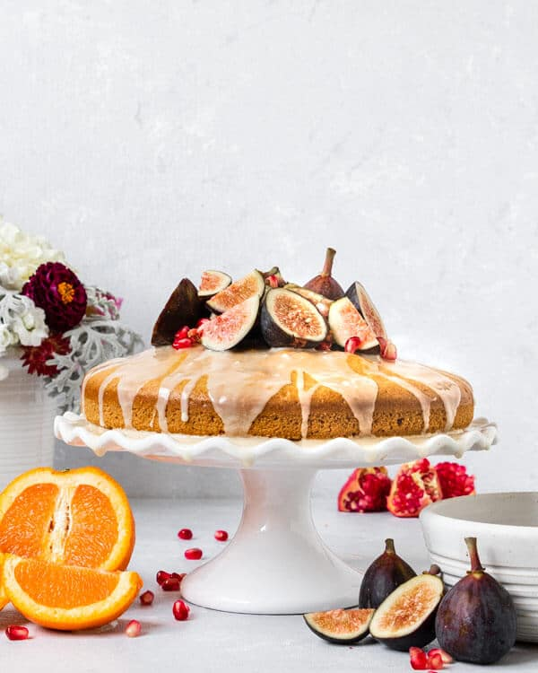 A cake stand topped with an orange blossom olive oil cake topped with orange glaze, fresh figs, and fresh pomegranate seeds