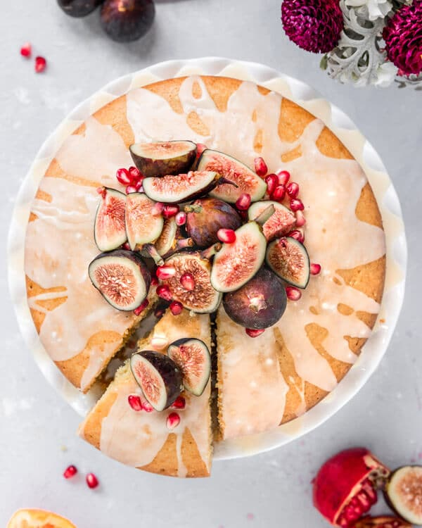 cake with figs and pomegranate on top on a cake stand with a slice cut out
