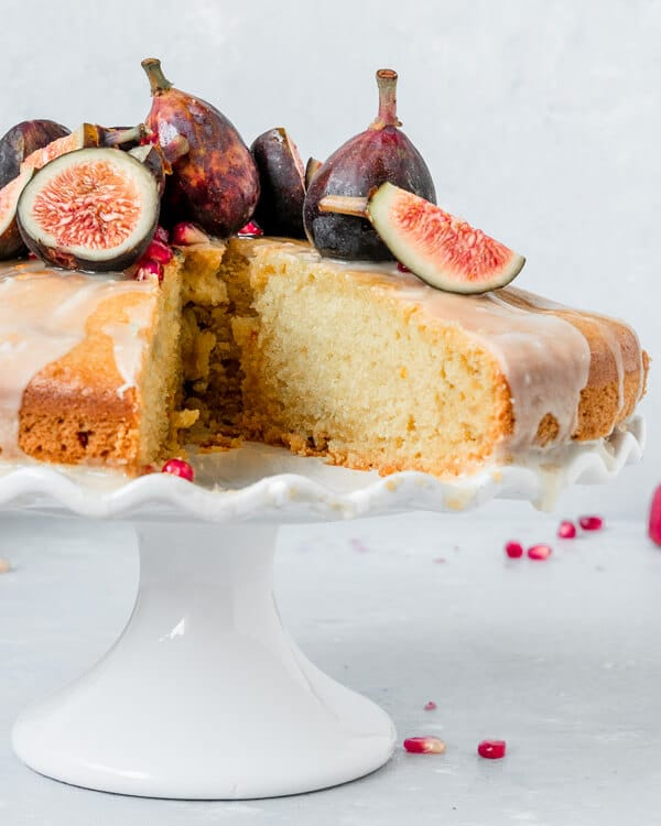 A slice of orange blossom olive oil cake on a cake stand topped with figs and pomegrante