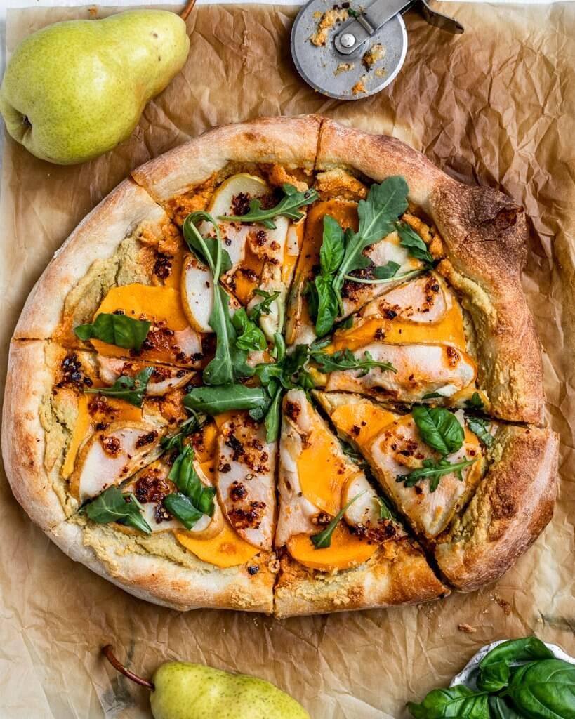 Vegan Pear Pizza with a creamy garlic sauce ,bartlett pears, butternut squash, arugula, basil, and a drizzle of chili oil. #pearpizza