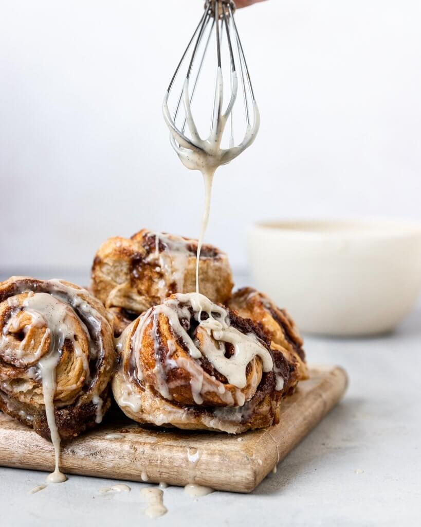 A stack of gooey warm vegan sourdough cinnamon rolls topped with vanilla bean glaze