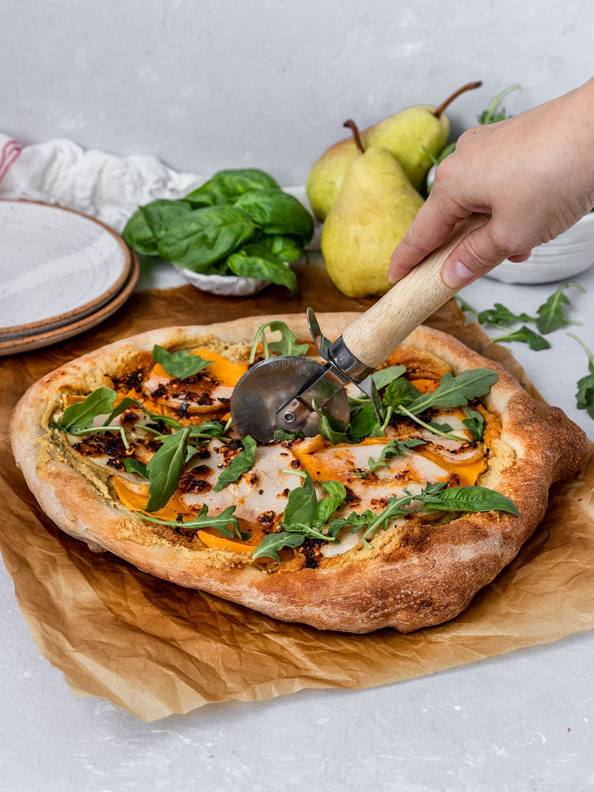 butternut squash, pear, arugula pizza being sliced with pizza cutter