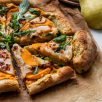 slices of pizza with butternut squash, pear, chili oil, and arugula on top of parchment paper