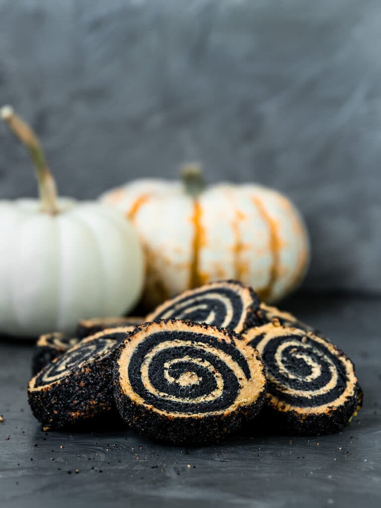 orange and black pinwheel swirl cookies with pumpkins in background