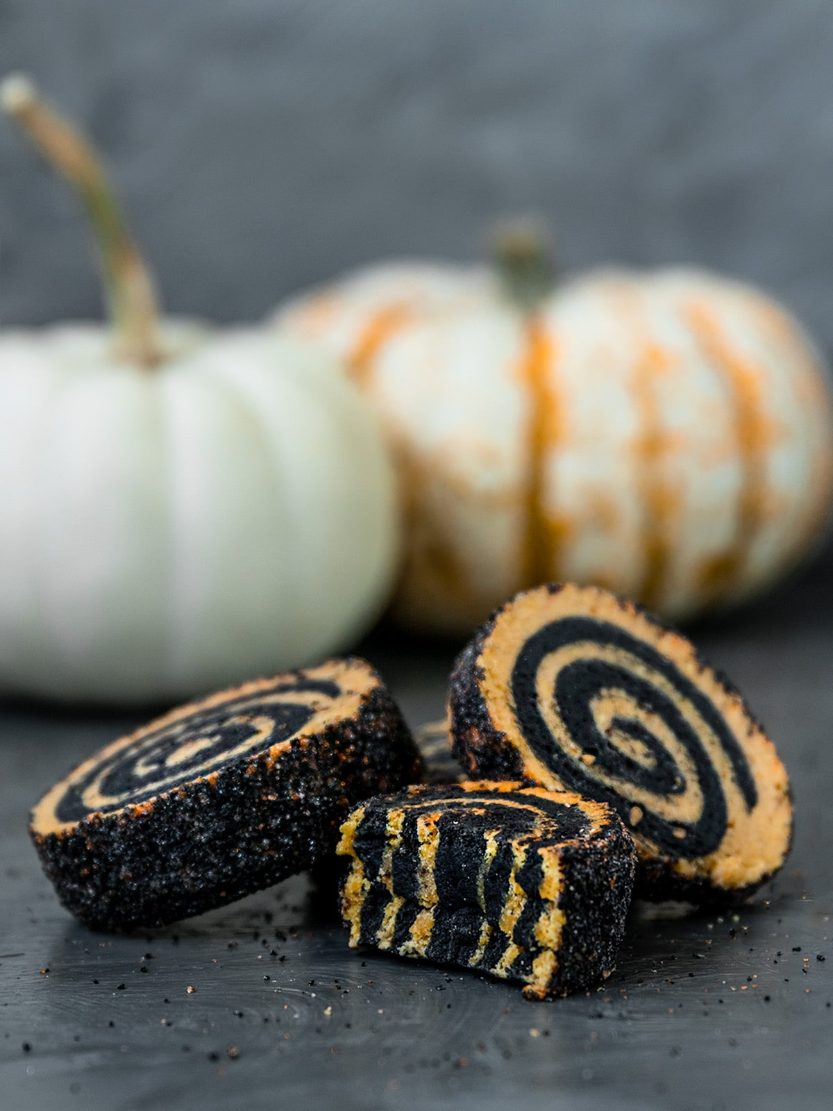 three pinwheel cookies one cut in half to show layers of black and orange swirls inside