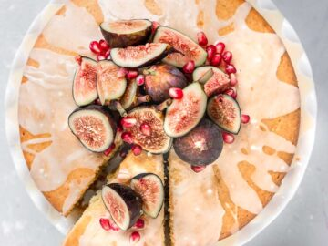 Vegan Orange Blossom Cake topped with orange glaze, fresh figs, and pomegranate with a slice cut out