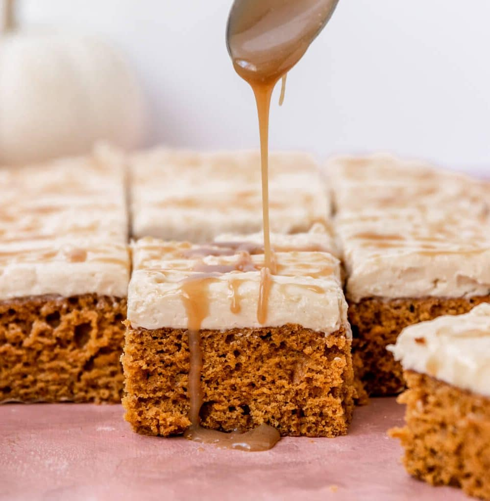 A slice of Vegan Pumpkin Cake topped with salted caramel frosting and getting drizzled with a spoonful of salted caramel