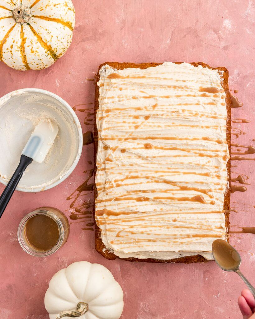 Pumpkin Sheet Cake with salted caramel frosting getting a spoon-full of additional salted caramel on top
