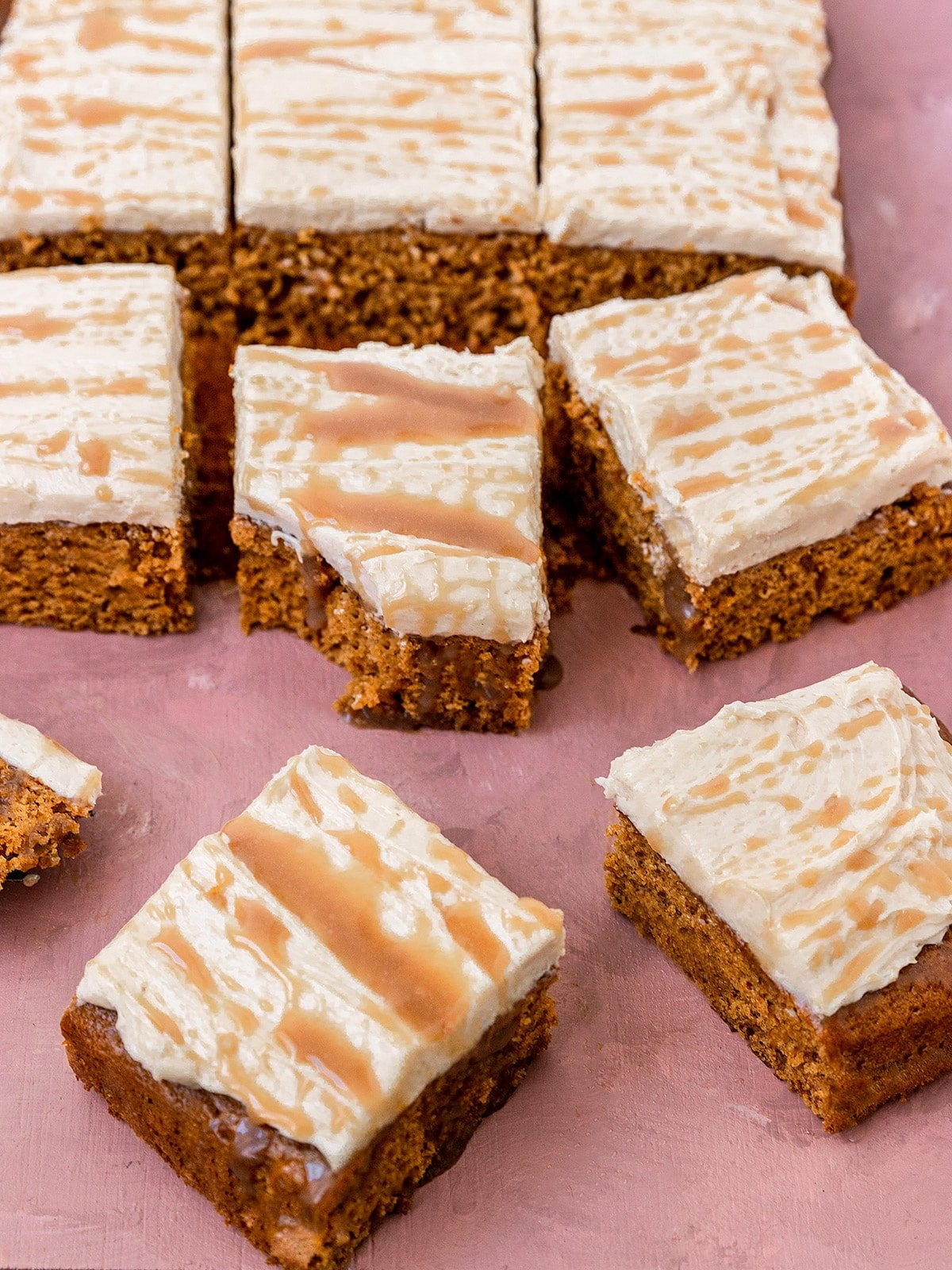 square slices of pumpkin sheet cake with a bite taken out of one piece