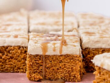 a piece of pumpkin sheet cake being drizzled with a spoonful of caramel
