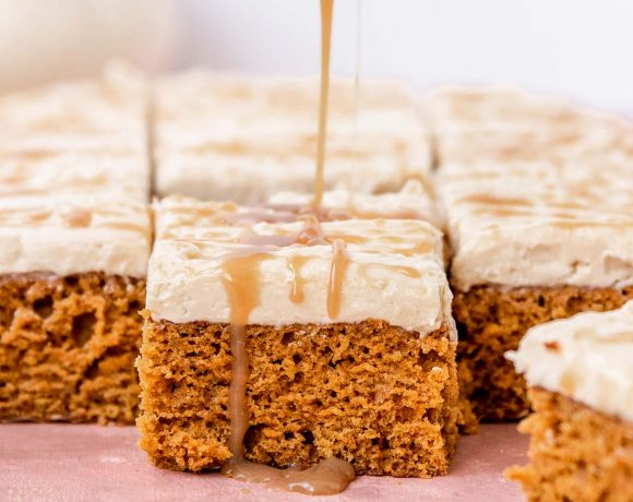 A slice of vegan pumpkin sheet cake topped with salted caramel frosting getting a spoonful of salted caramel poured on top