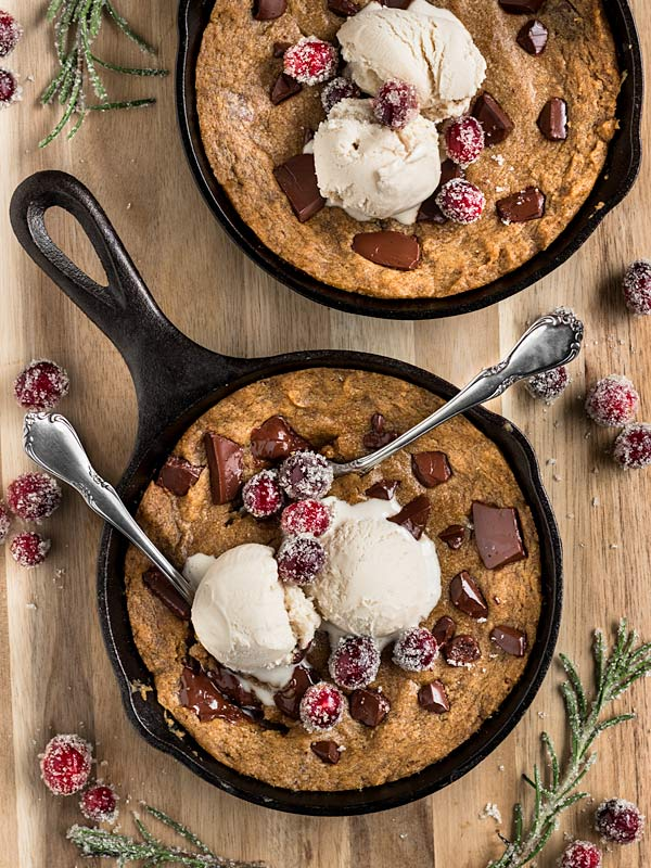two cast iron skillets filled with gingerbread cookie dough topped with vegan ice cream and sugared cranberries
