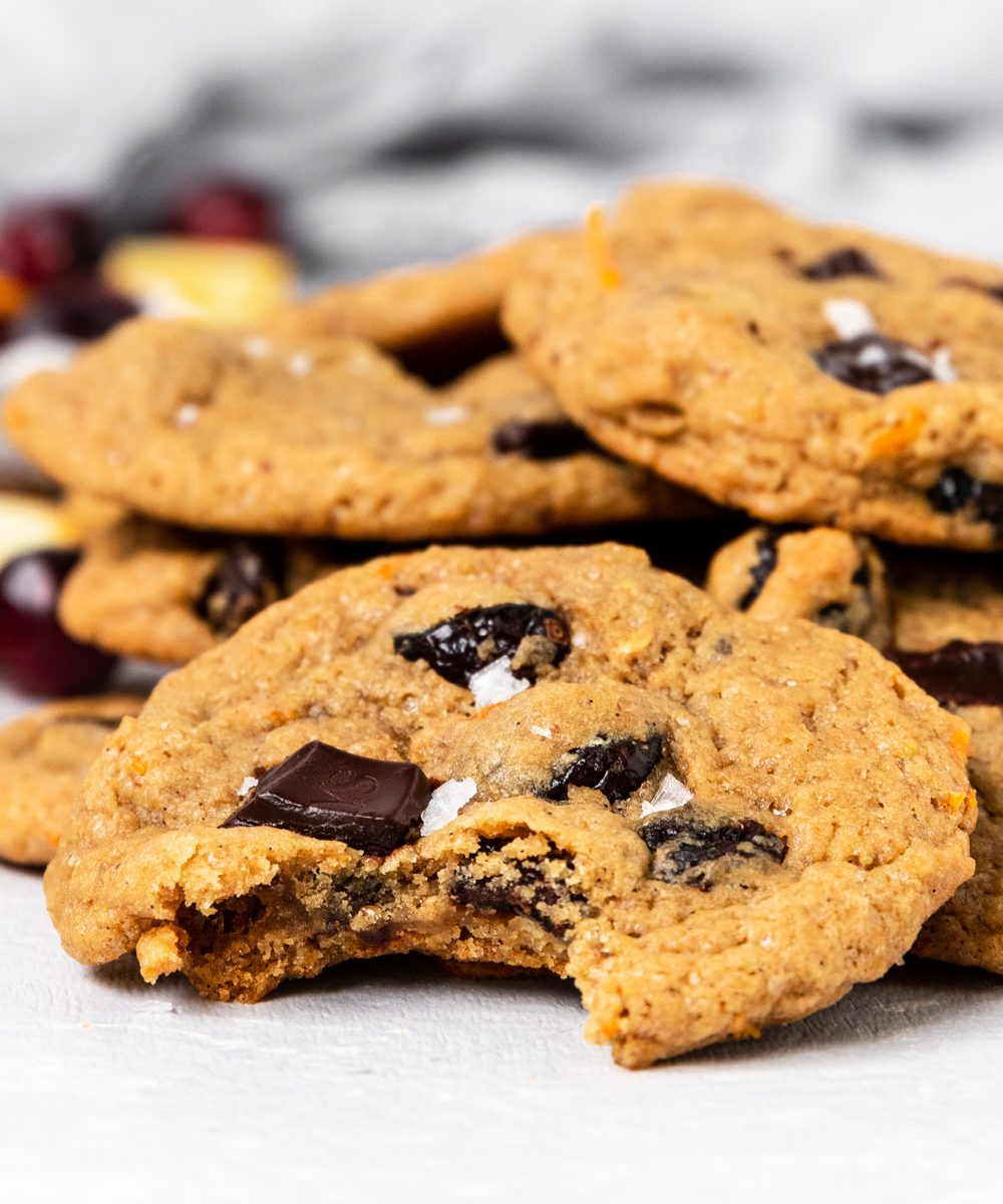 Cranberry Orange Chocolate Chip Cookie with a bite taken out on a stack of cookies