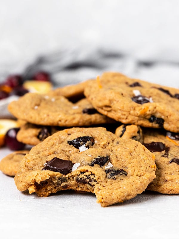 Cranberry Orange Chocolate Chunk Cookie with a bite taken out on a stack of cookies