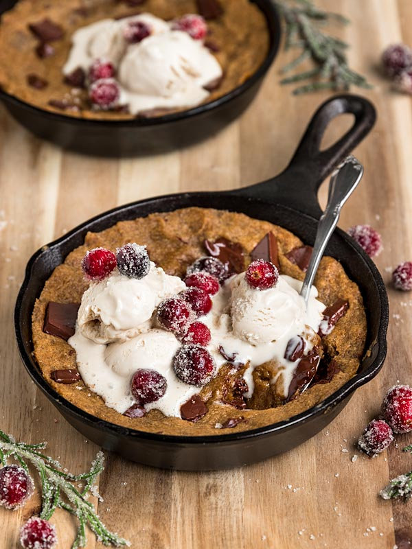 cast iron skillet gingerbread cookie with chocolate chips topped with vanilla ice cream and sugared cranberries