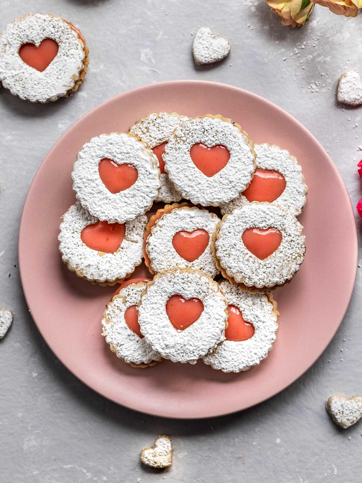 plate of heart shaped linzer cookies with pink filling