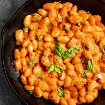 a cast iron skillet filled with gnocchi in a tomato sauce with fresh basil on top