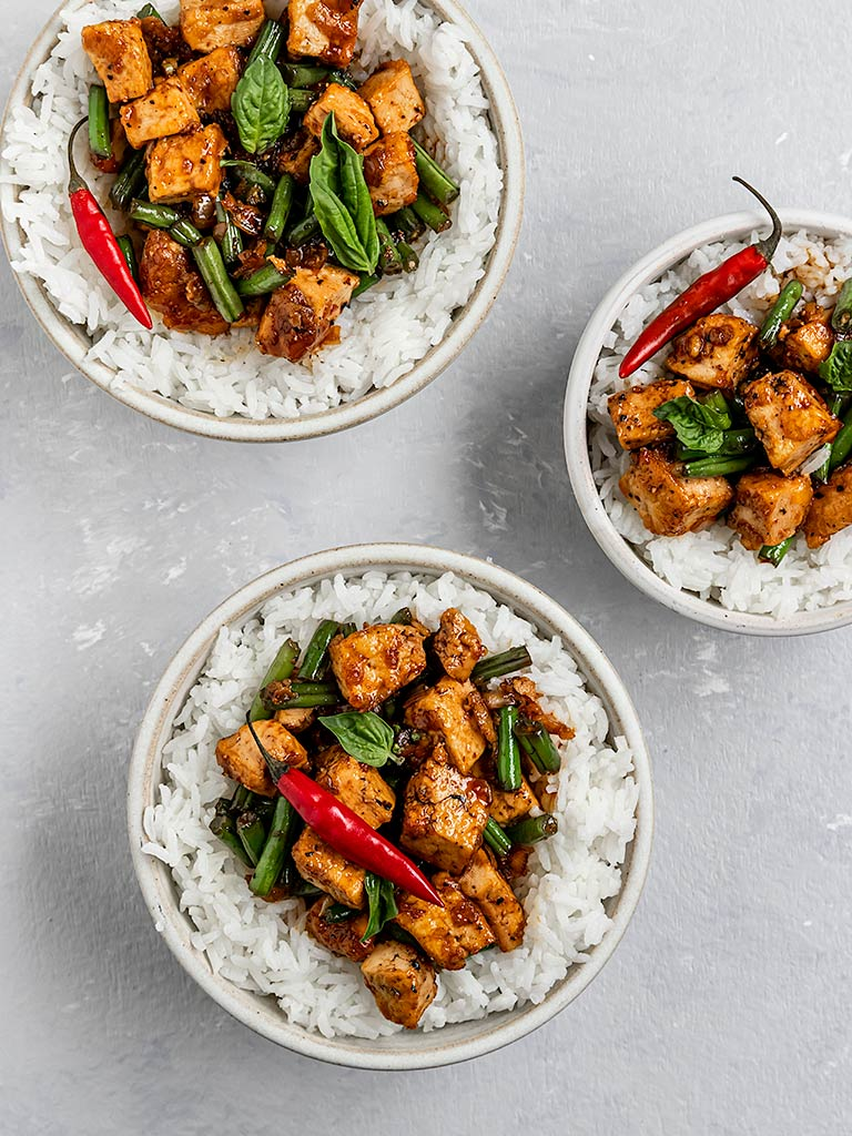three bowls filled with white rice, black pepper tofu, green beans, and thai chili peppers