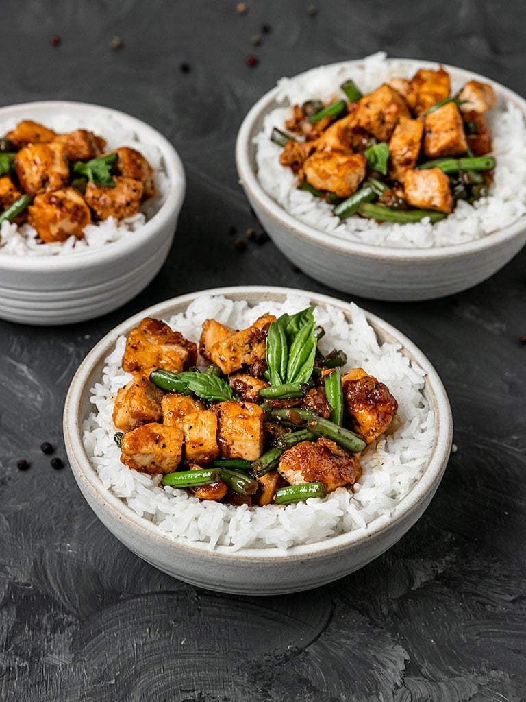 three bowls filled with white rice, black pepper tofu, green beans, and basil
