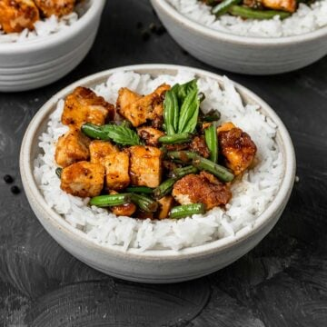 A bowl of white rice filled with black pepper tofu, green beans, and basil