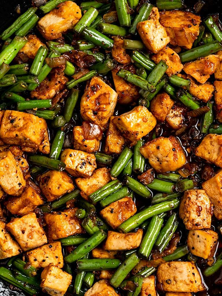 black pepper tofu green bean stir fry in a cast iron wok