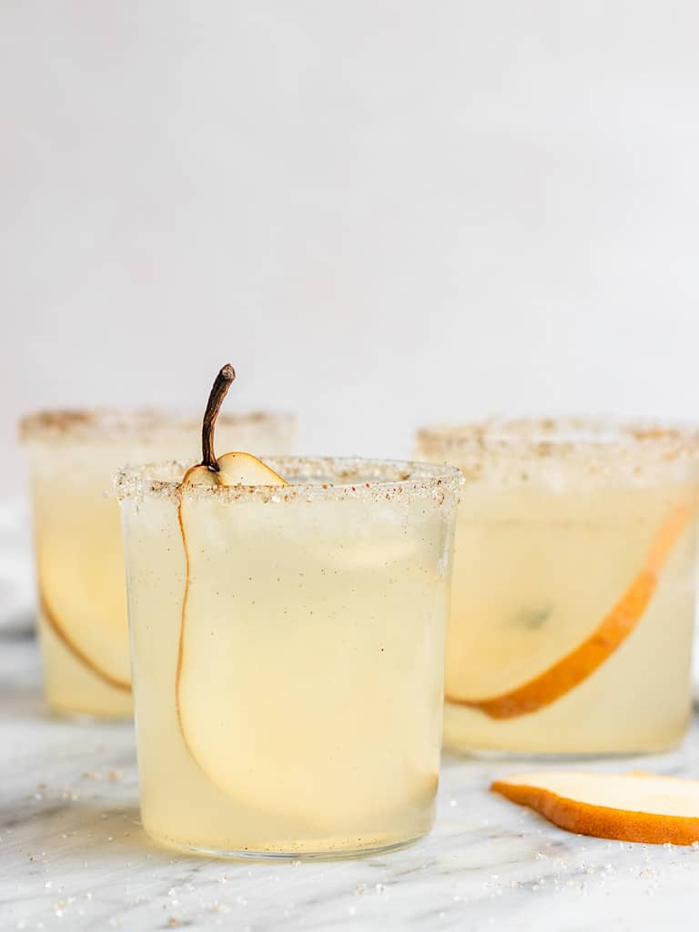 three gin fizz pear cocktails with pear slices and vanilla syrup