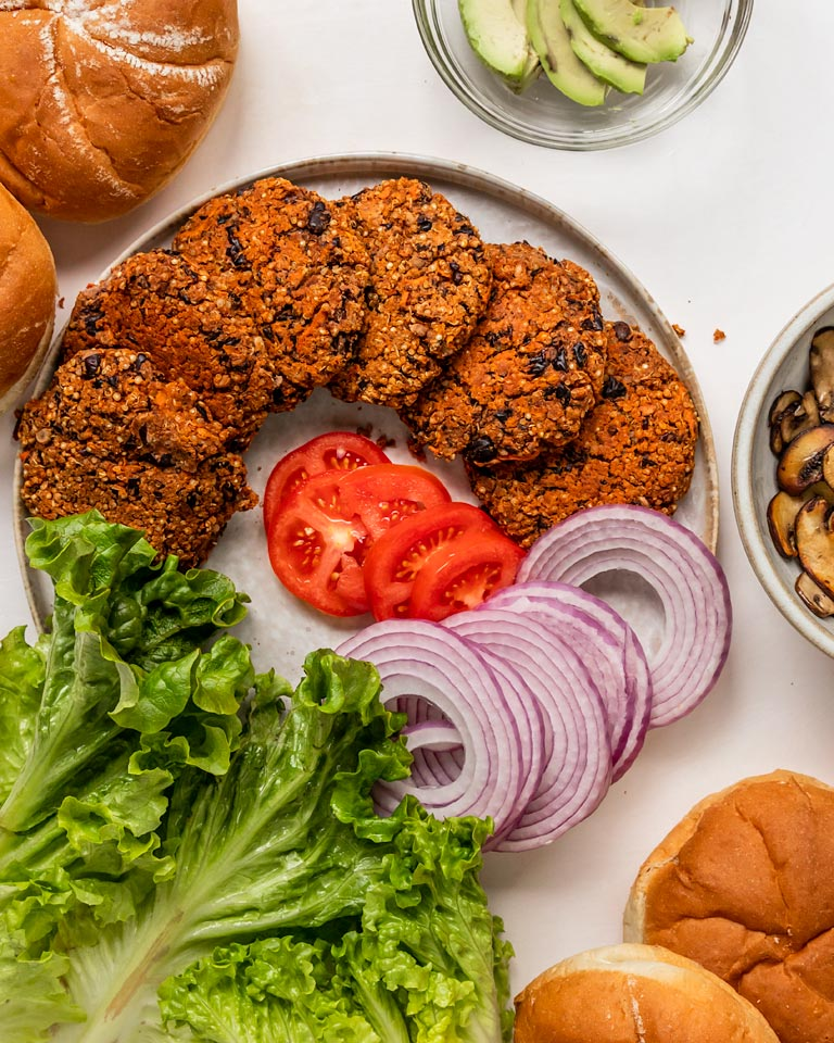 black bean quinoa veggie burgers with burger ingredients like lettuce, tomato, red onion, mushrooms, and burger buns
