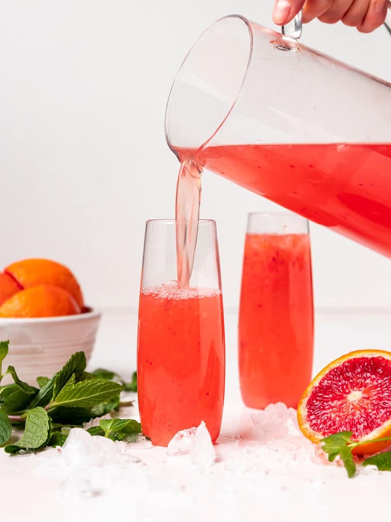 a glass being filled with blood orange mimosa pitcher