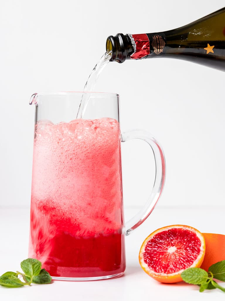pitcher of blood orange juice and mint syrup being filled with prosecco