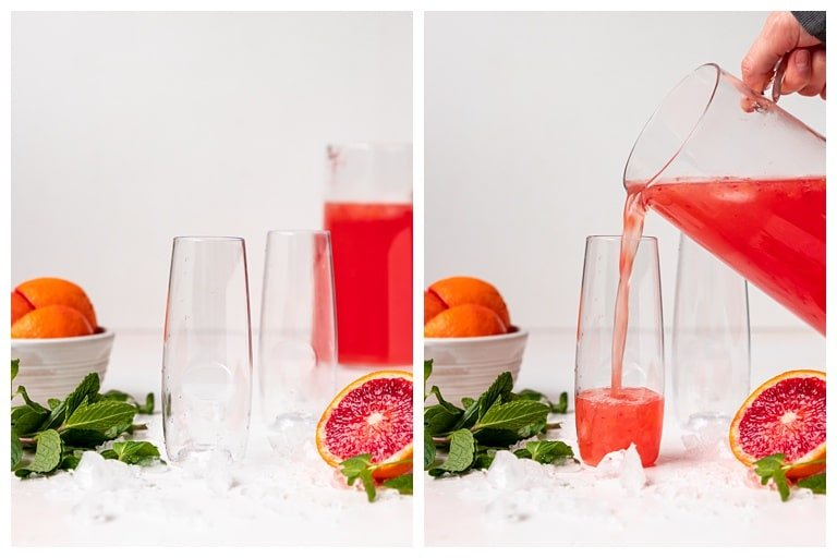 blood orange mimosas being poured from a pitcher into two glasses