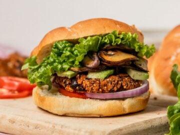 burger bun filled with black bean quinoa burger, mushrooms, avocado, lettuce, onion, an tomato