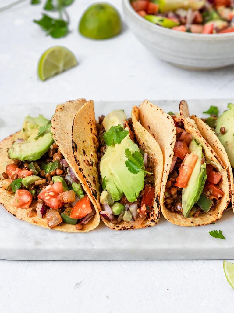 three lentil tacos with avocado, pico de gallo, lime, and cilantro
