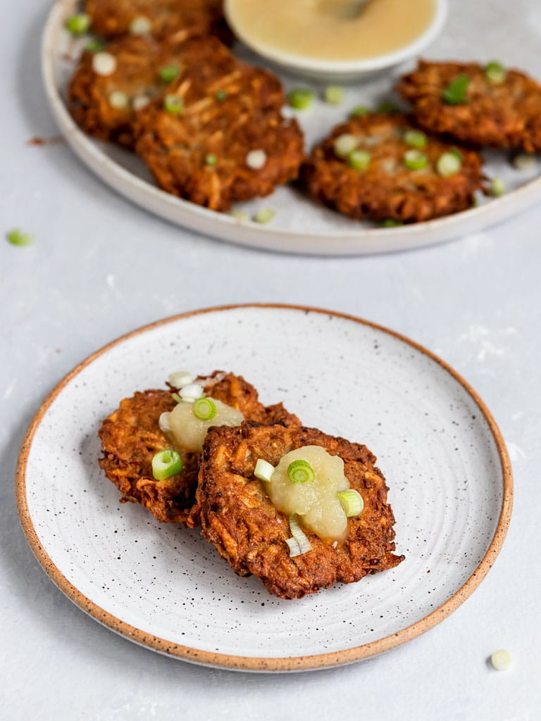 two potato latkes on a plate with apple sauce and scallions
