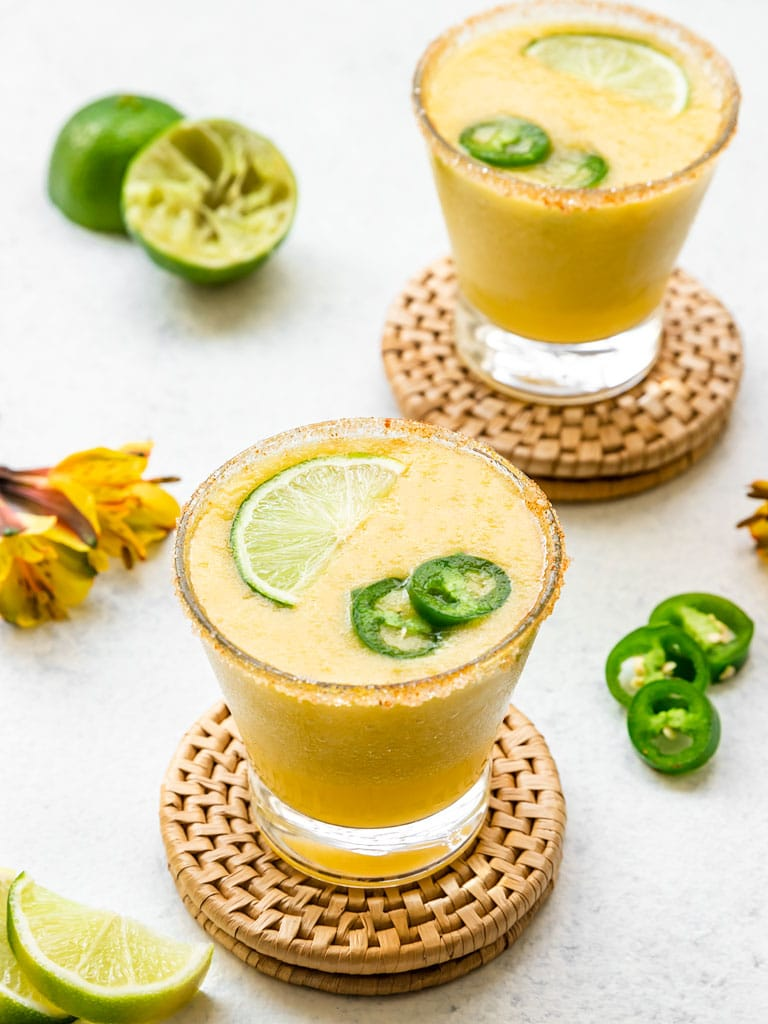 two frozen mango margaritas with jalapeno and lime and a chili salt rim