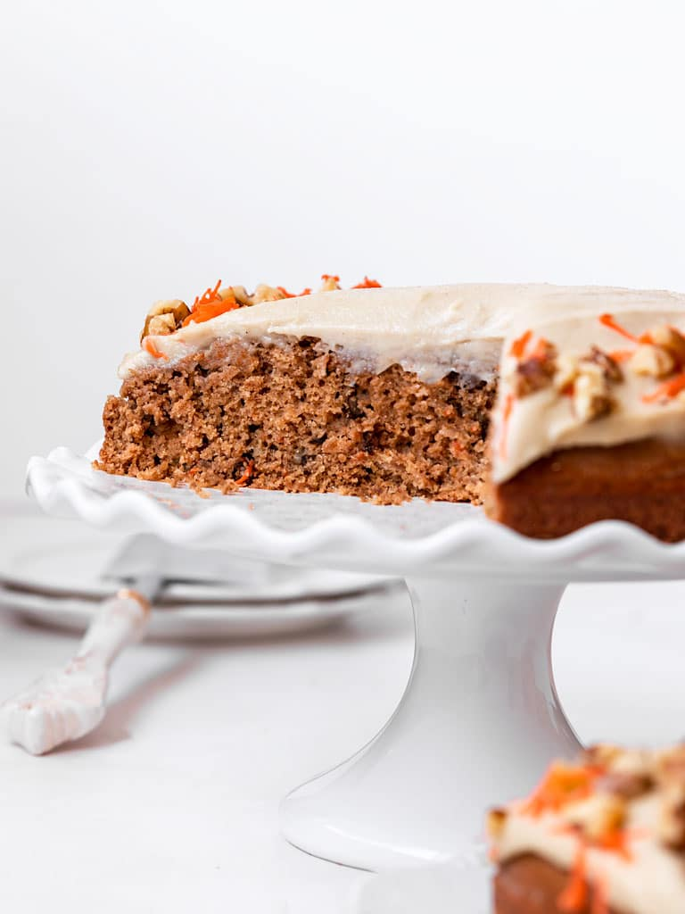 carrot walnut cake on cake stand with slices cut out