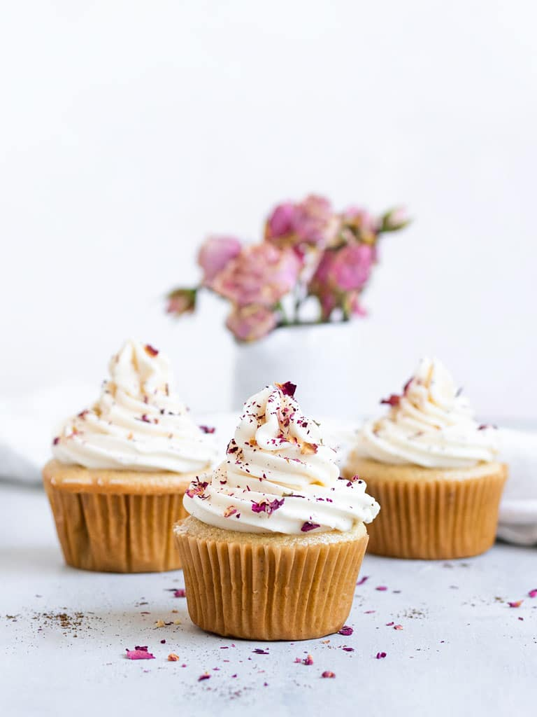 three cardamon vanilla cupcakes with frosting and rose petals