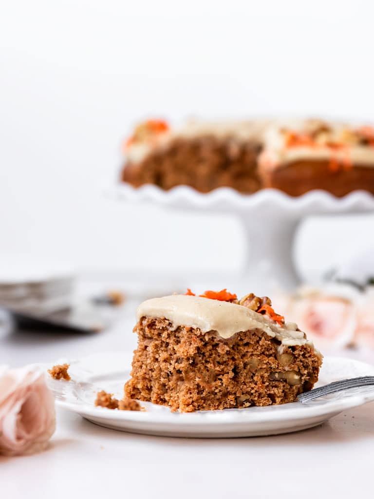 a slice of vegan carrot walnut cake with a bit taken out