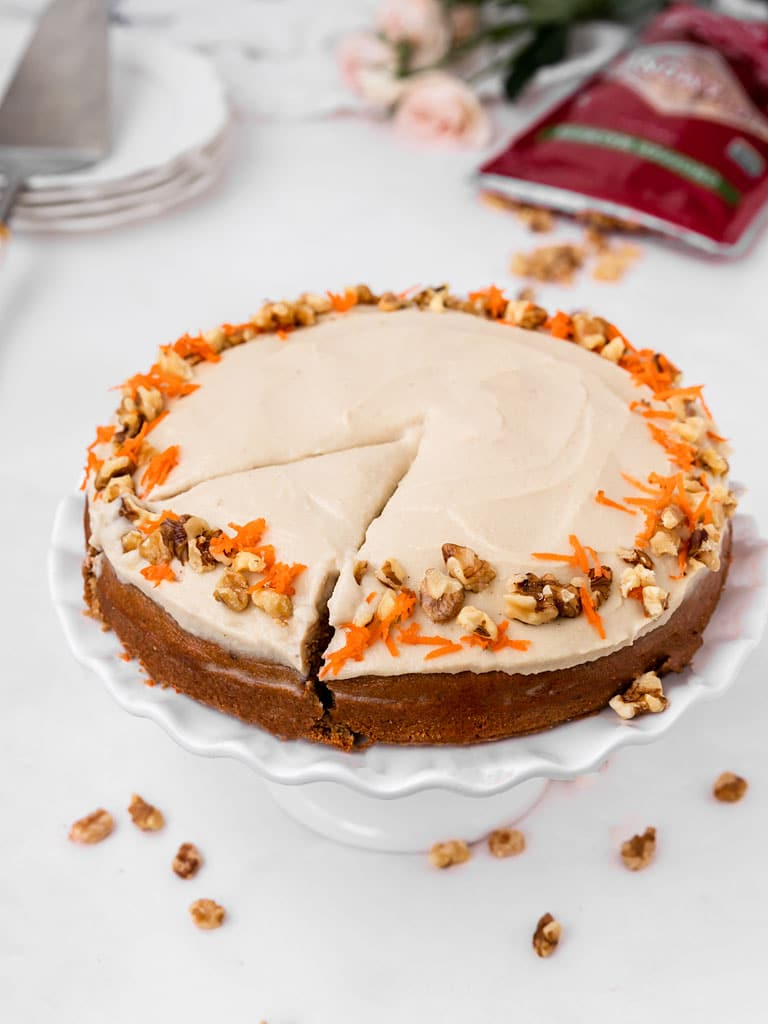 carrot walnut cake with cashew frosting, carrot, and walnut on top