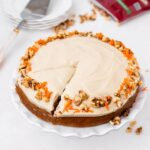 carrot walnut cake with frosting, carrot, and walnut on top