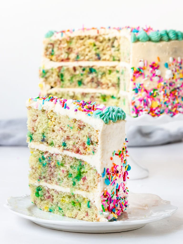 a slice of 3 layer funfetti sprinkle cake with vanilla buttercream
