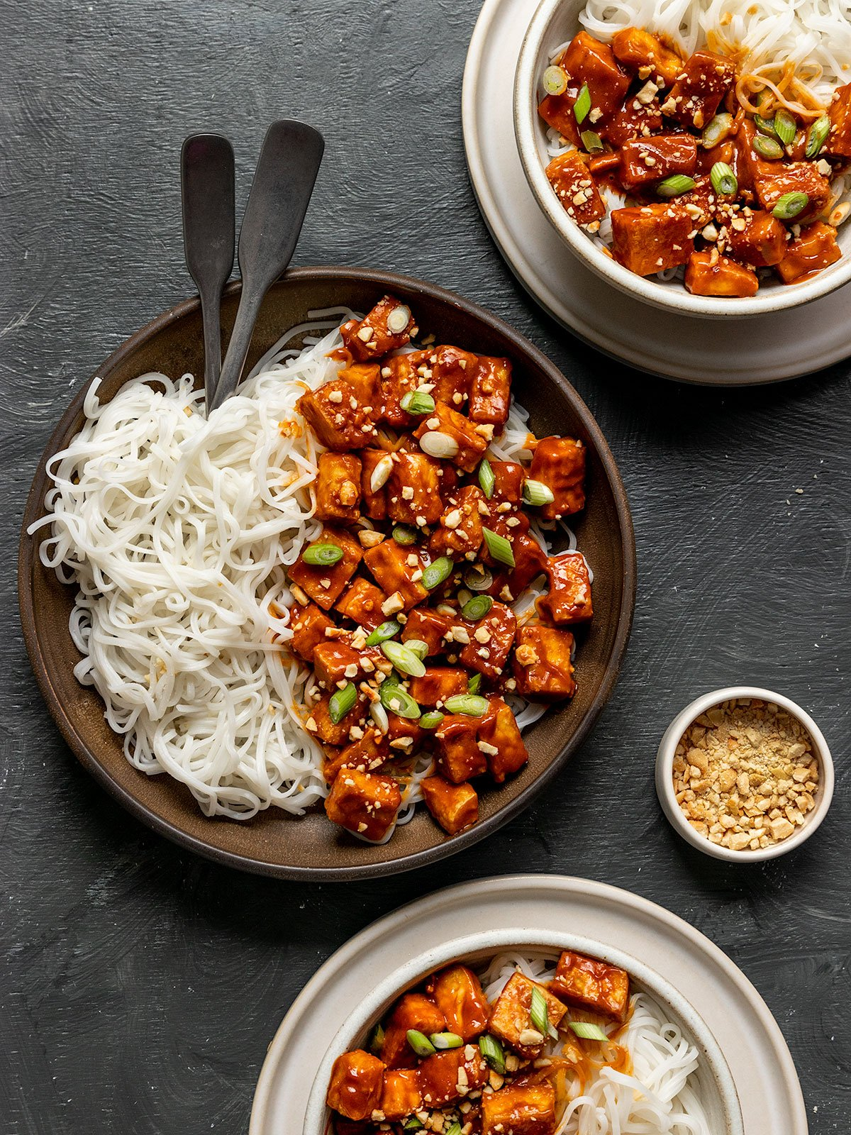 three bowls filled with peanut butter tofu on rice noodles