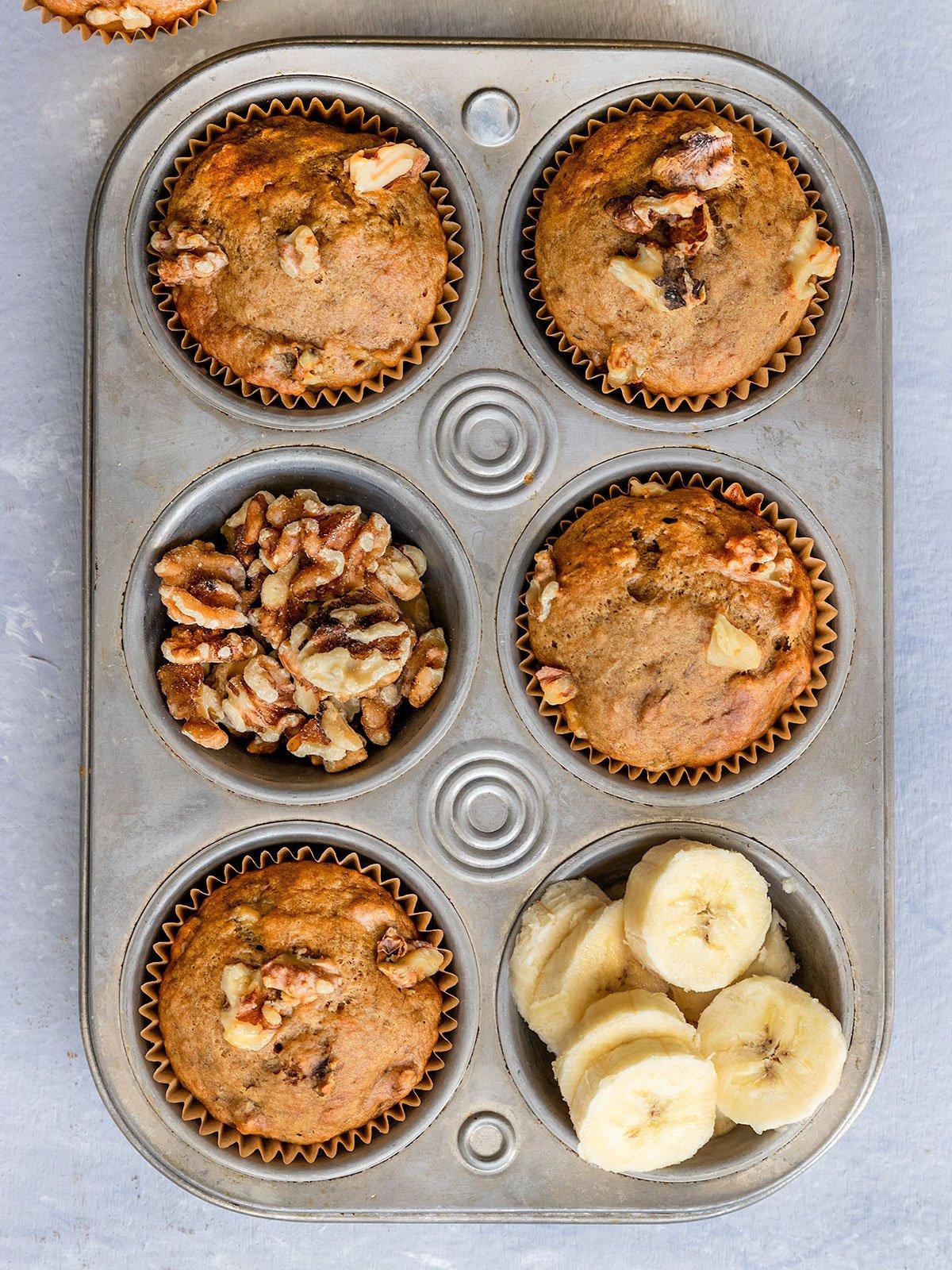 muffin tin full of banana muffins, walnuts, and banana slices