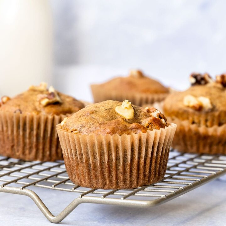 wire rack filled with banana walnut muffins and a glass of milk