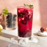 a cocktail glass filled with muddled blackberries, vodka, soda water, and mint