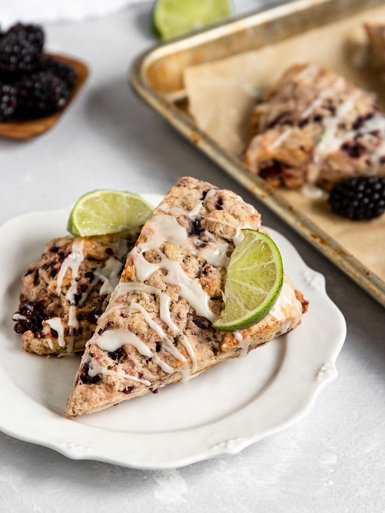 two blackberry scones with lime wedges on top on a plate