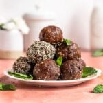 bliss balls stacked on a plate rolled in hemp seeds